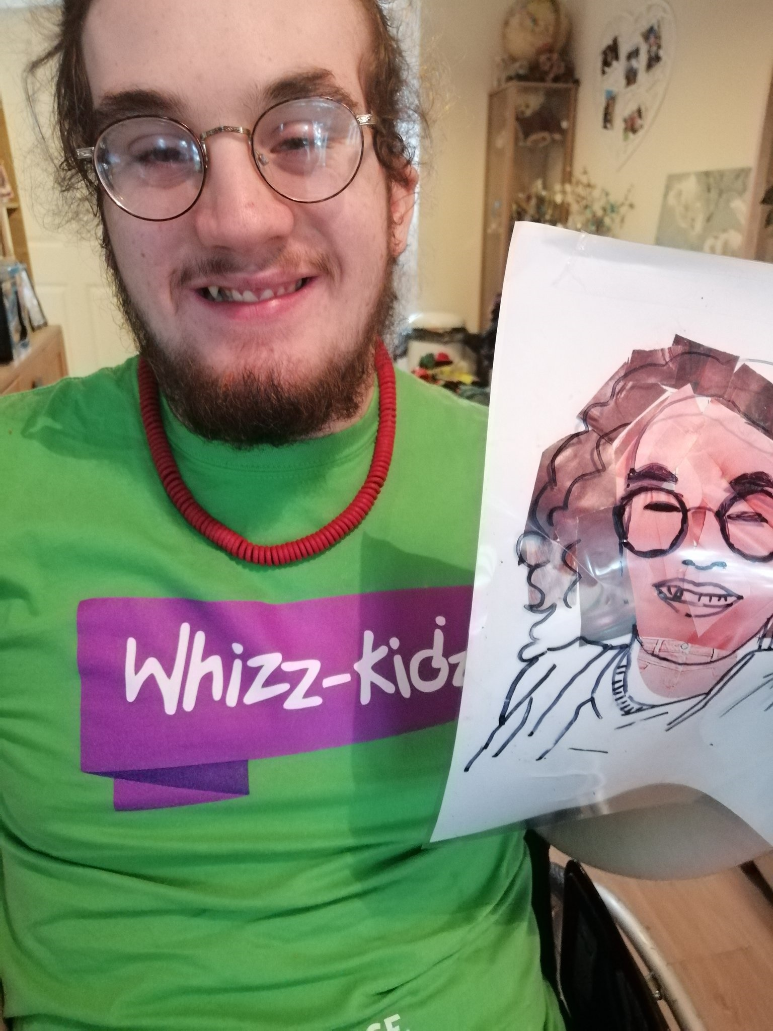 Owen holds up work from a Whizz-Kidz art workshop