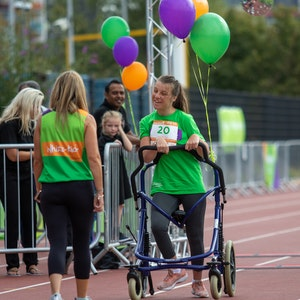 Abbie, with her walker,  and Michelle at Challenge 75, walking on the athletic track