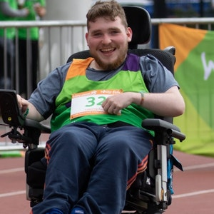 Young Man smiling in his powered wheelchair on the track at Challenge 75