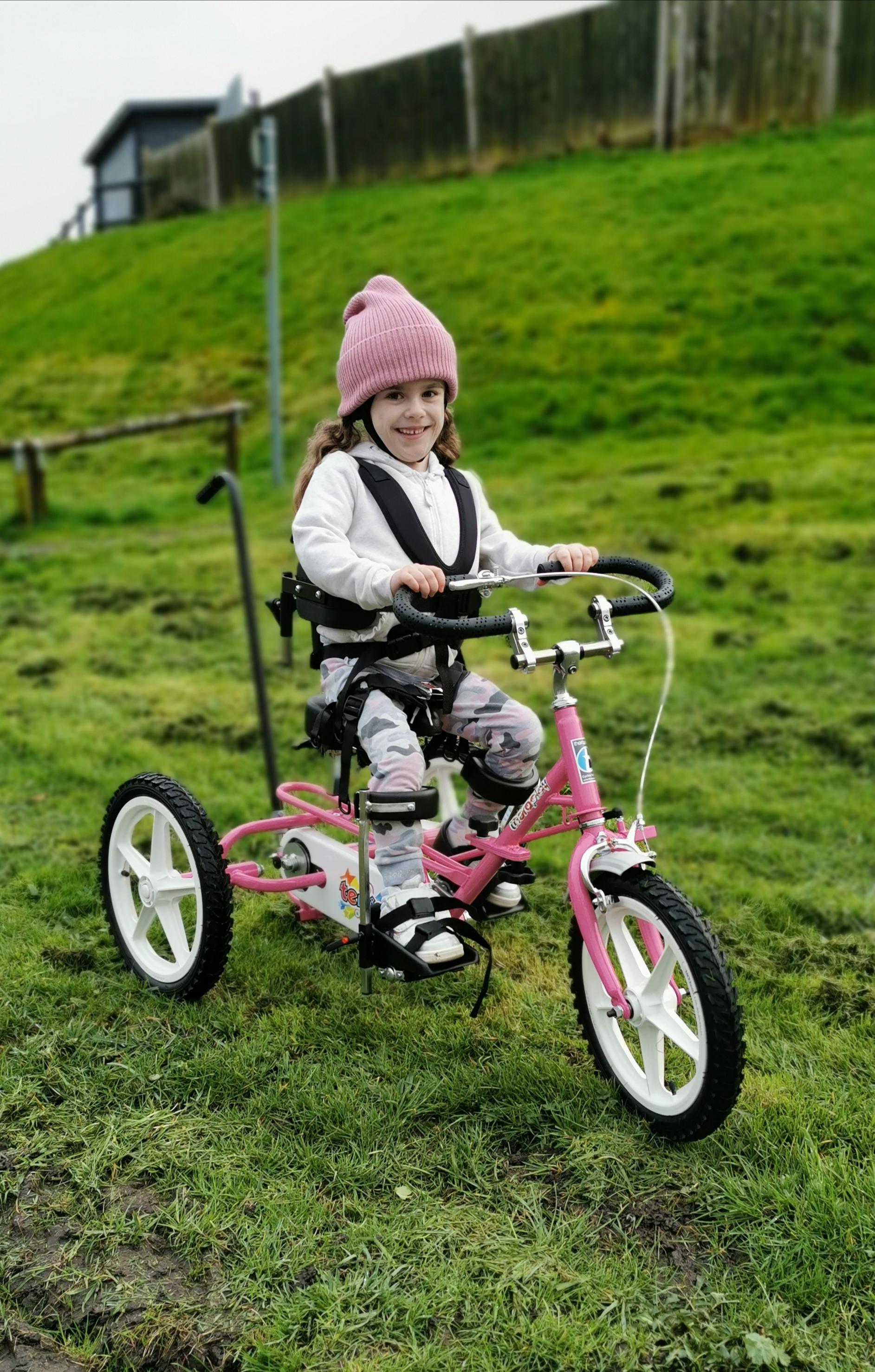Carmela smiles as she poses on her pink Whizz-Kidz trike
