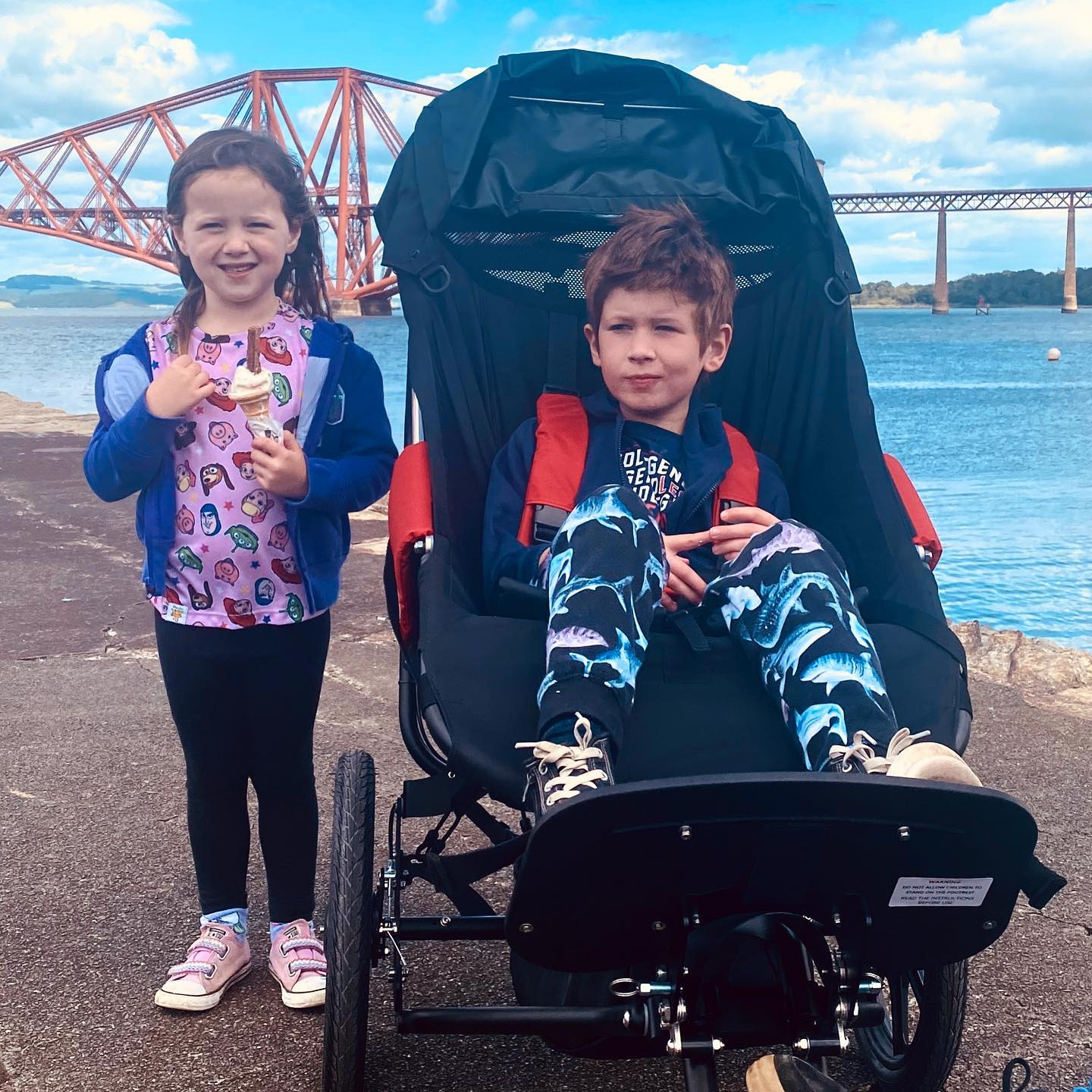 Brody in his Whizz-Kidz buggy with his little sister