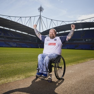 Chris, in his Bolton Wanderers shirt, smiles with his hands up in the air at the side of the pitch at the University of Bolton Stadium