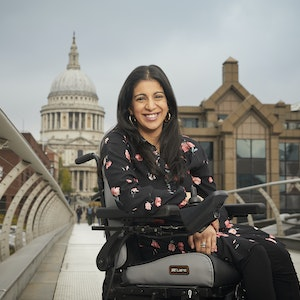 Arunima smiles in her powered wheelchair as she poses on London's Millenium Bridge in front of St Paul's Cathedral