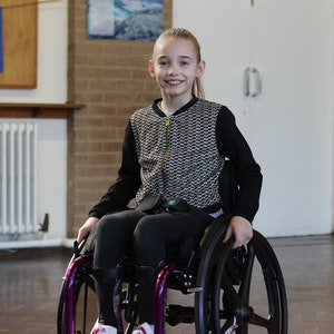 Adele smiles as she poses in her Whizz-Kidz manual wheelchair