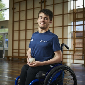 Louis smiles and holds boccia balls as he poses in his Boccia UK t-shirt