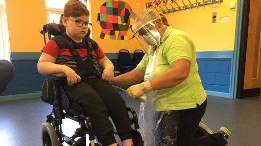 A Whizz-Kidz mobility therapist completes a wheelchair handover in PPE