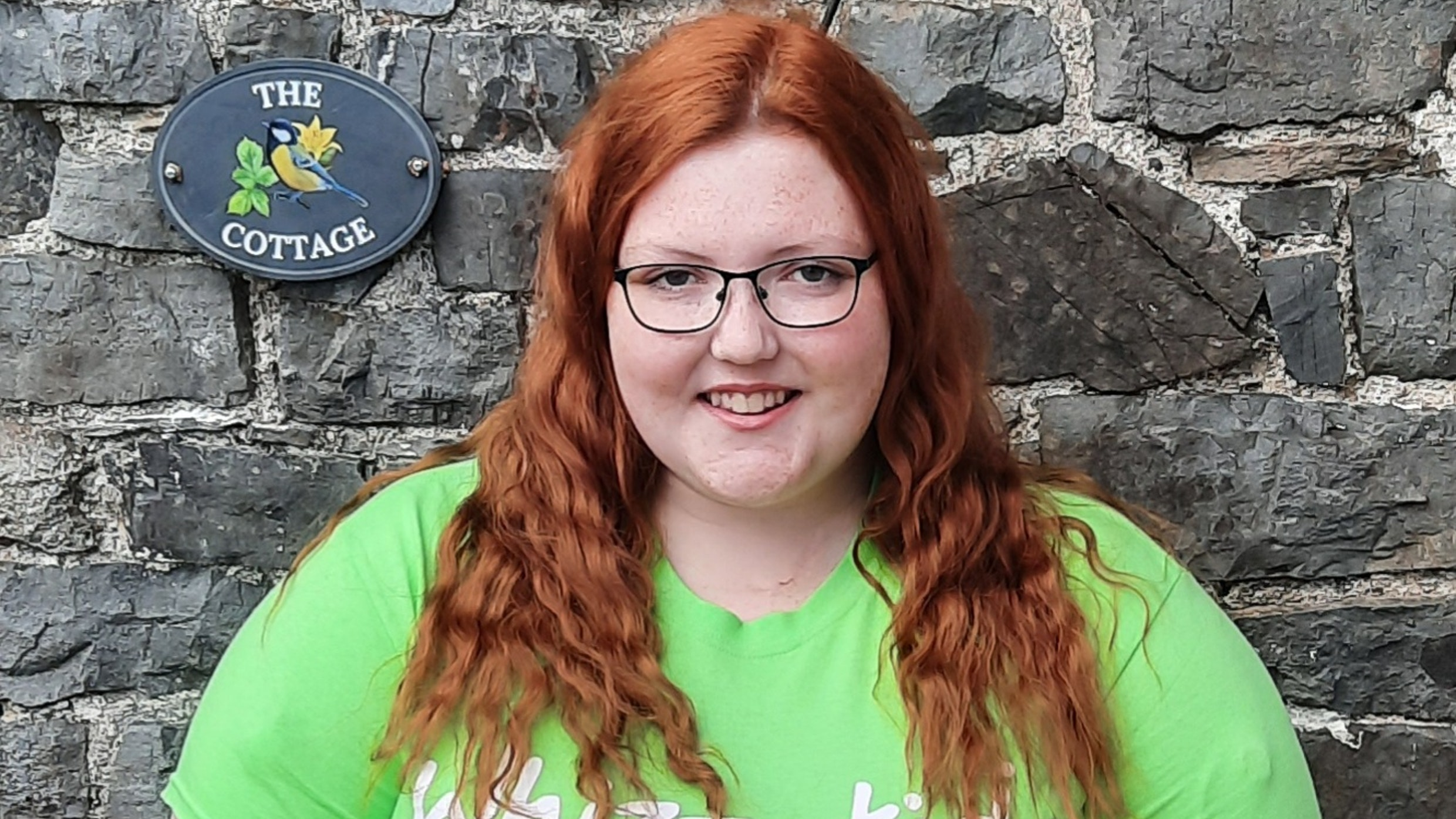 Sophie poses in a green Whizz-Kidz t-shirt