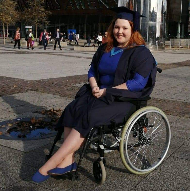 Sophie poses in a cap and gown on her graduation day