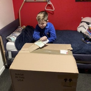 Zach opens a box containing his new Whizz-Kidz wheelchair