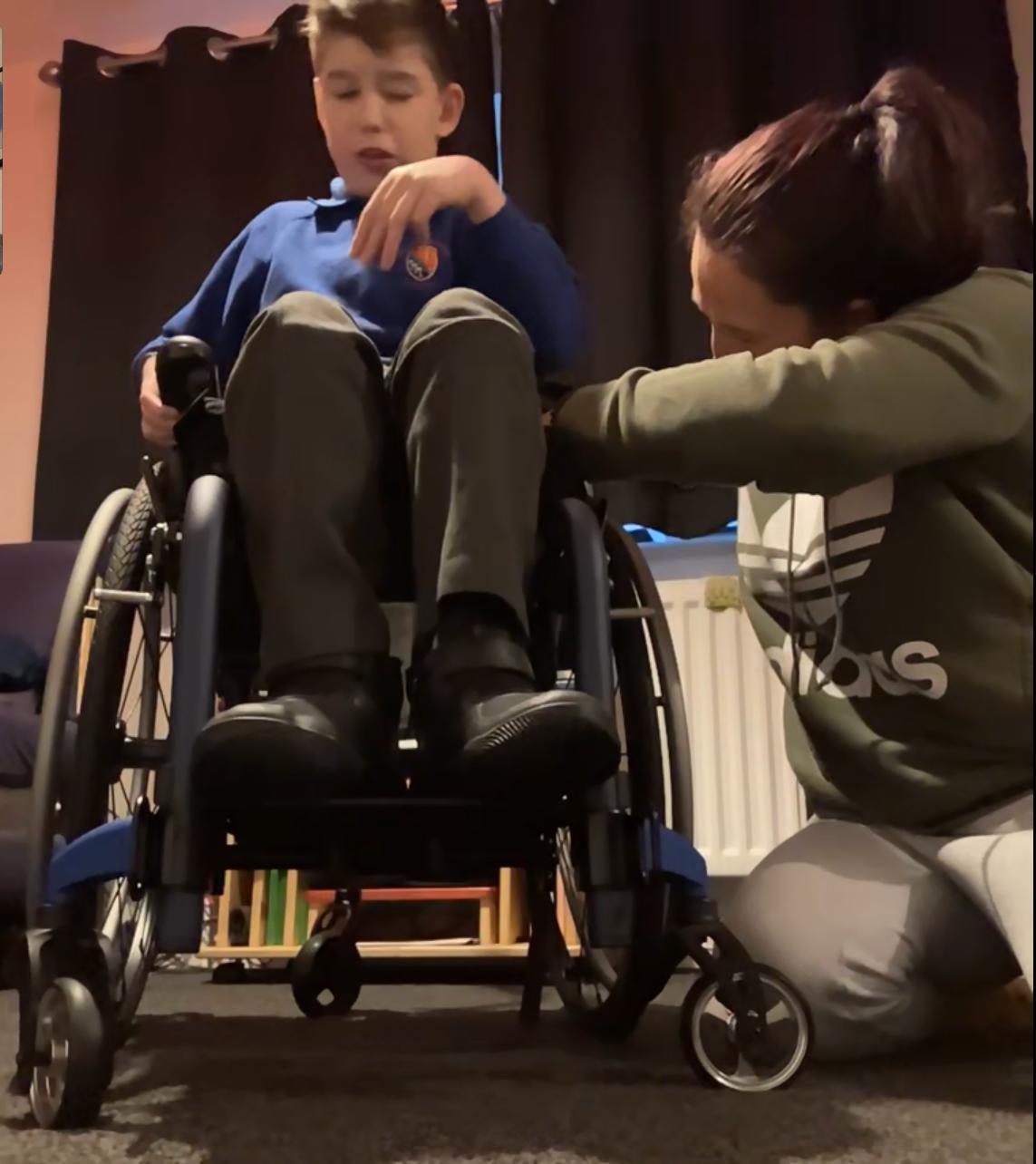 Mum Samantha helps fit Zach's new wheelchair in a remote handover