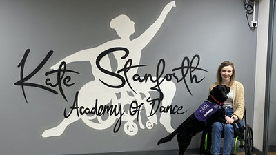 Kate Stanforth in her wheelchair with her guide dog at her academy of dance school