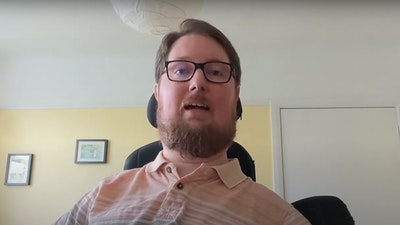 A screenshot of Miro talking about personal finance. He is wearing a peach polo shirt with white stripes, black glasses and has a beard.