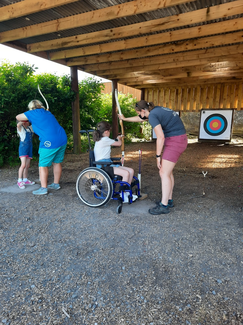 Young wheelchair users take part in archery while at a Whizz-Kidz club