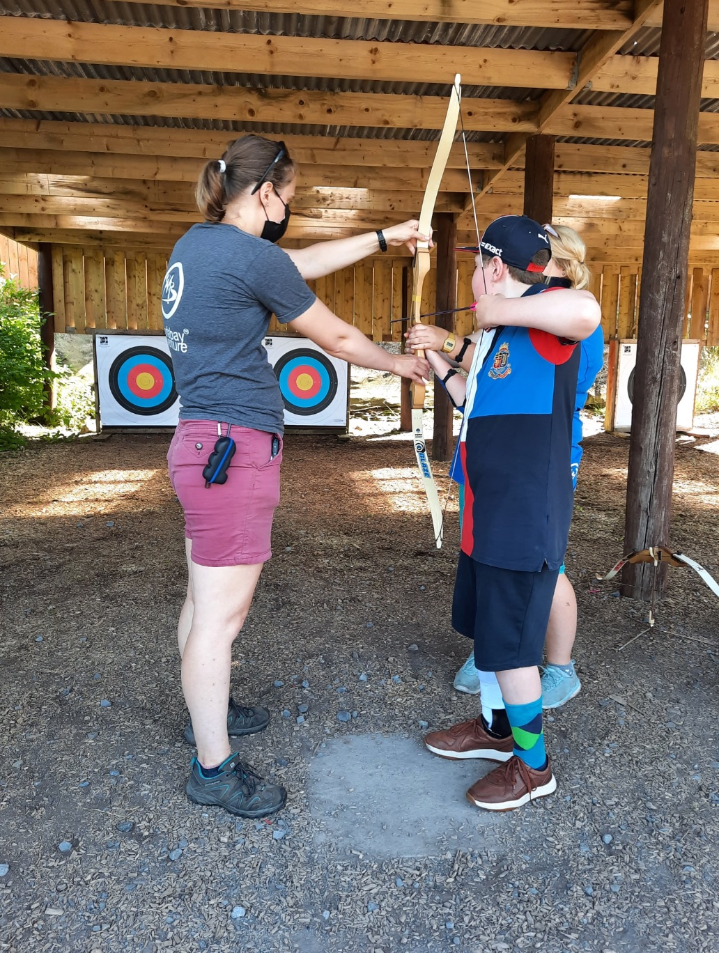 A young person takes part in archery at a Whizz-Kidz club