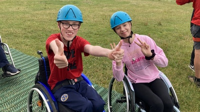 Two young wheelchair users, wearing blue helmets, smile while giving a thumbs up and peace signs at a Whizz-Kidz ziplining club