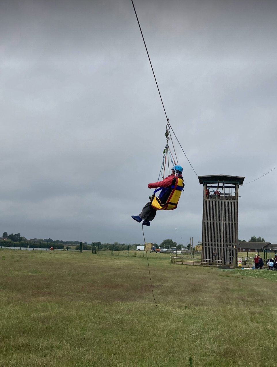 A young person sits in a harness while enjoying ziplining at a Whizz-Kidz club