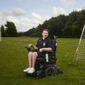Nathan, wearing a black referee kit and white trainers, smiles as he poses in his powered wheelchair in front of a football goal