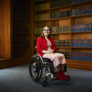 Penny, in her manual wheelchair, smiles at the camera while in a library