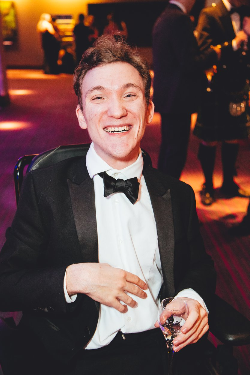 Sam smiles at the camera while wearing a tuxedo