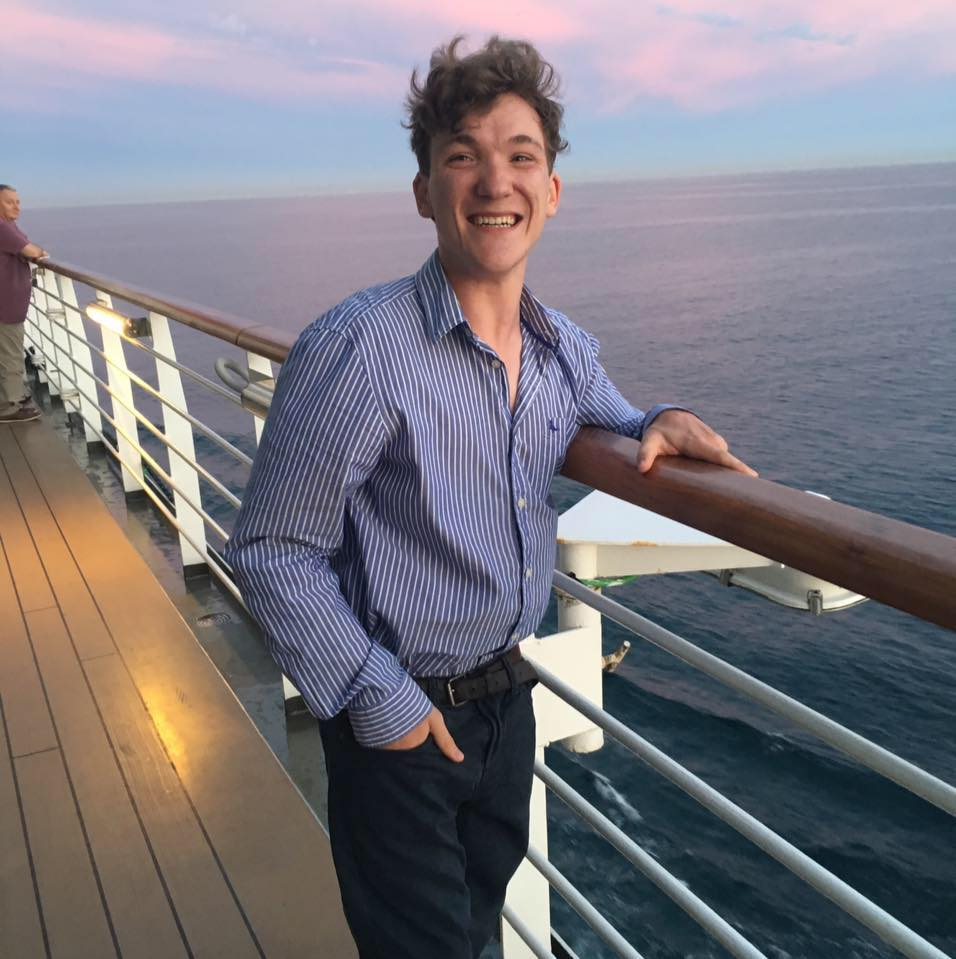 Sam smiles while standing on a balcony overlooking the sea