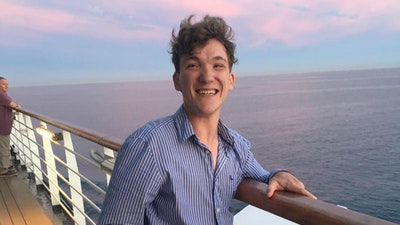 Sam stands on a balcony overlooking the sea