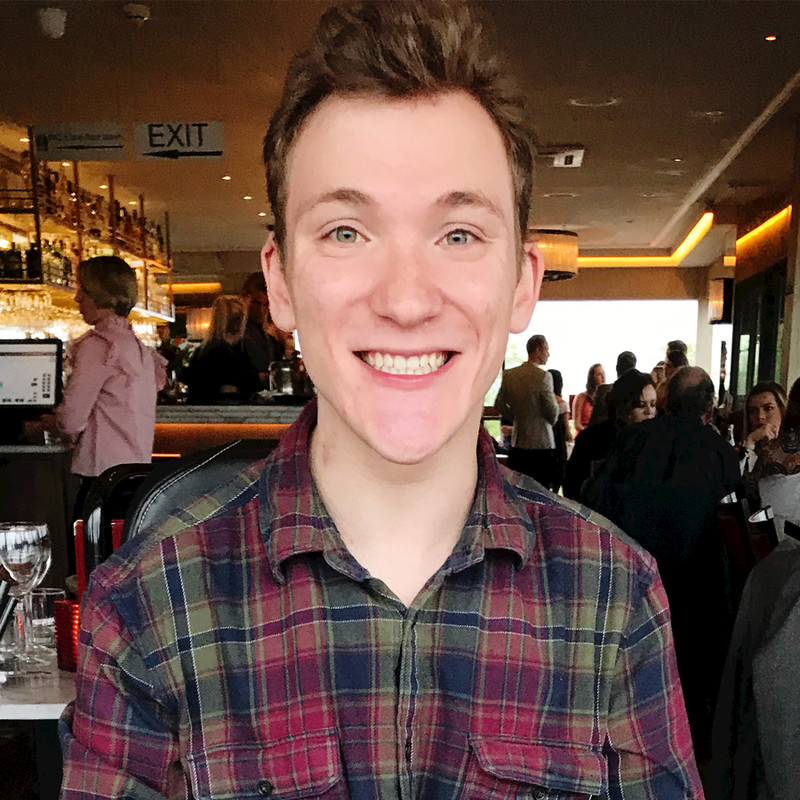 Sam, in a restaurant, smiles at the camera while wearing a checked shirt