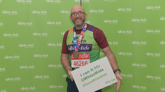 Man holding board that says 'I ran it for Whizz-Kidz'