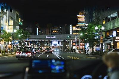 Tags: road, tarmac, metropolis, urban, city, downtown, car, person, intersection, lighting
