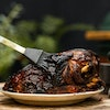 Stainless steel silicone brush basting a pork shoulder