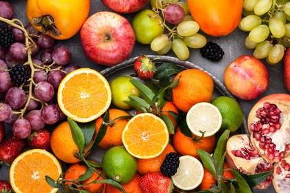 A variety of citrus fruits and berries on a table and in a platter