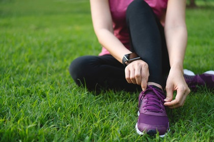 Woman sitting on lawn in workout clothes tying her sneaker