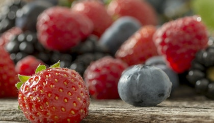 An assortment of strawberries, blueberries, raspberries and blackberries on a wooden table