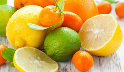 Assorted citrus fruits such as lemons, limes oranges, kumquats are shown whole, in halves and sliced, on a wooden table.