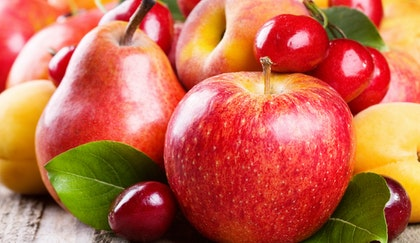 Assorted stone fruits, such as apples, cherries, pears, nectarines, peaches, plums and combined on a wooden table