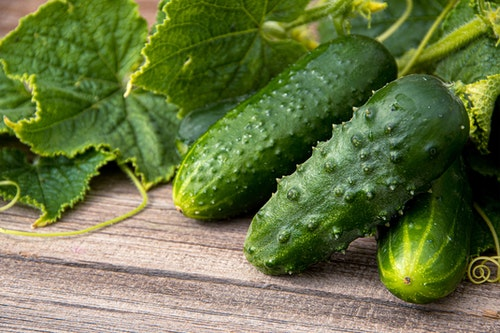 3 cucumbers with leaves from their plant on a wooden table