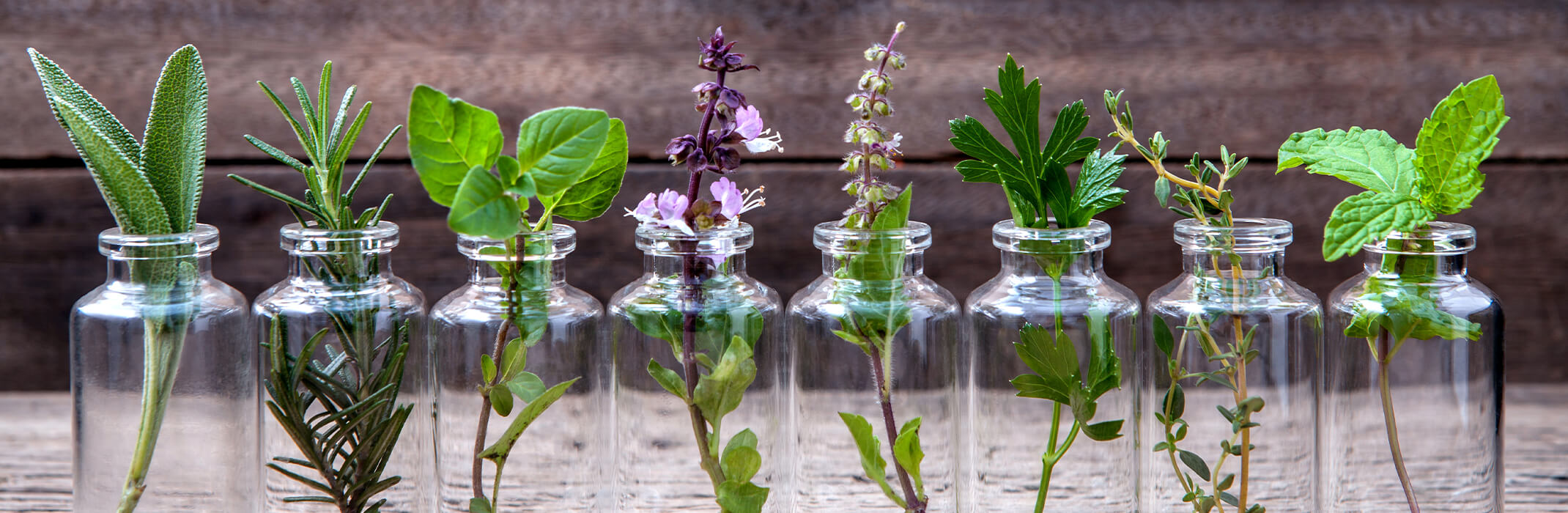 A variety of herbs - each in a clear glass bottle on a wooden table