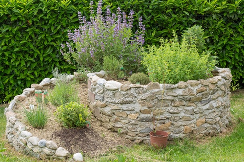 A circular raised herb garden made with stones