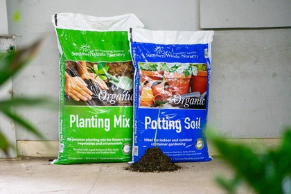 2 bags of soils - SummerWinds Nursery's Organic Planting Mix and Potting Soil with blurred plants in the foreground and a small pile of soil in front of the bags with a small plant in it