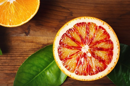 Half of a blood orange on a wood taben with plant leaves and half of a regular orange in the left corner