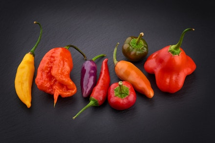 A variety of colorful hot peppers on a black surface
