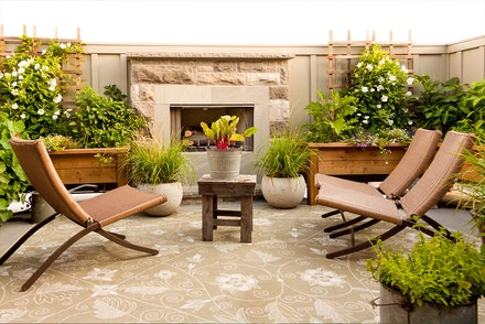 A patio with an outdoor rug and fireplace, seating and a wide variety of potted plants and flowers