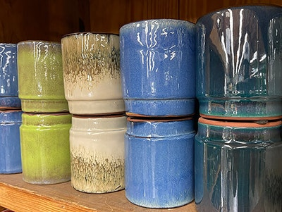 Assorted colors of stacked indoor pottery on a shelf