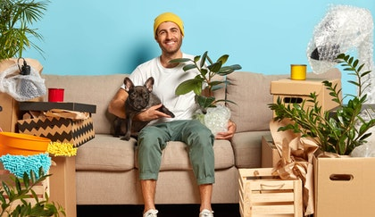 Man sitting on his couch with dog in one hand and rubber tree plant in the other smiling while in the midst of his things all still in a packed up state