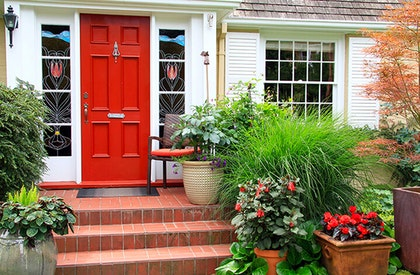 Front door of a home showing off beautiful landscape down brick steps with potted plants around