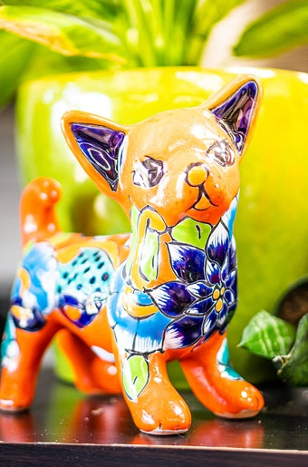 A closeup of a colorful Talavera animal with a potted houseplant in the background