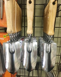 Multiple hand shovels hanging from pegs on a wall