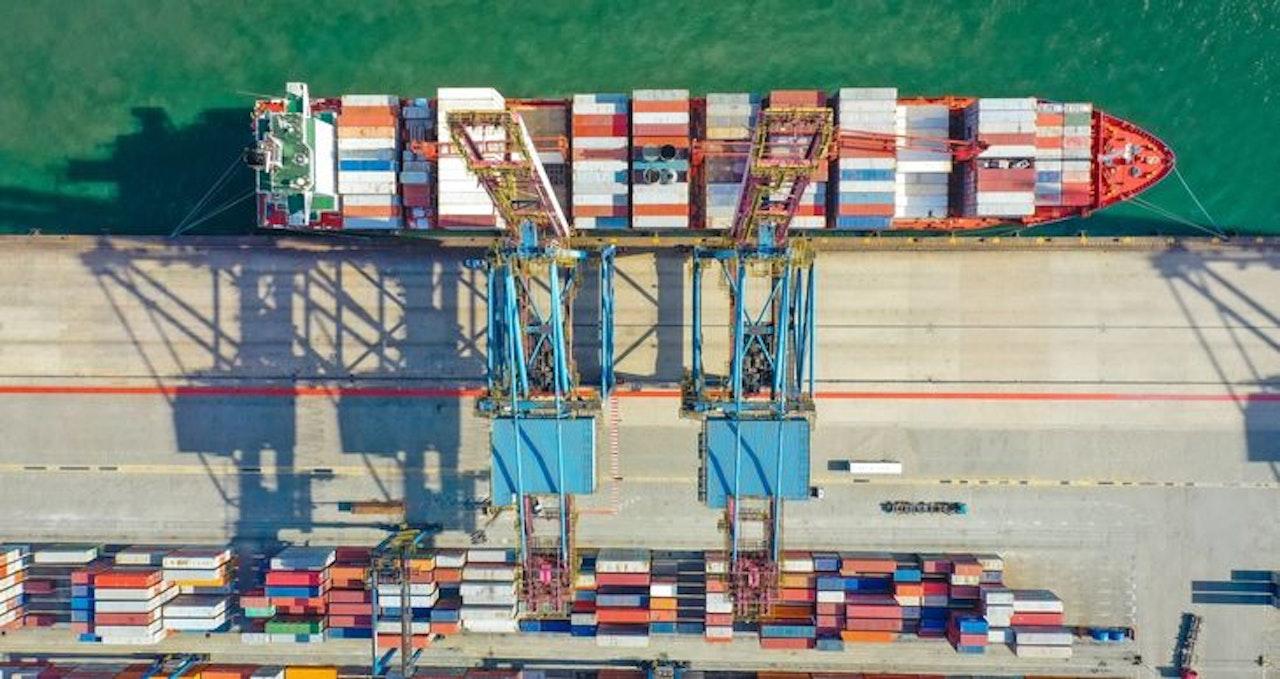 Containerschip wordt geladen met twee hijskranen