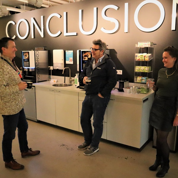 Drie collega's lachen en praten met een kop koffie in de hand