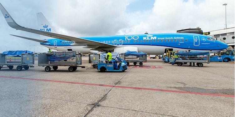 Een KLM vliegtuig staat naast de gate en wordt ingeladen