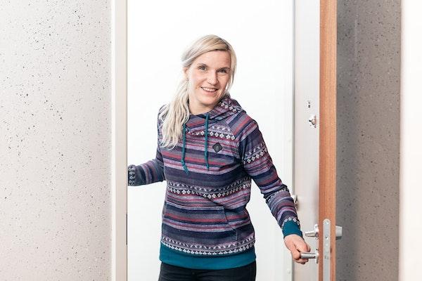 Nuori nainen  vuokra-asuntonsa ovella
